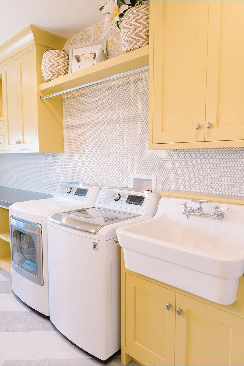 Yellow Shaker Laundry Room Cabinets with White Hex Tile Backsplash
