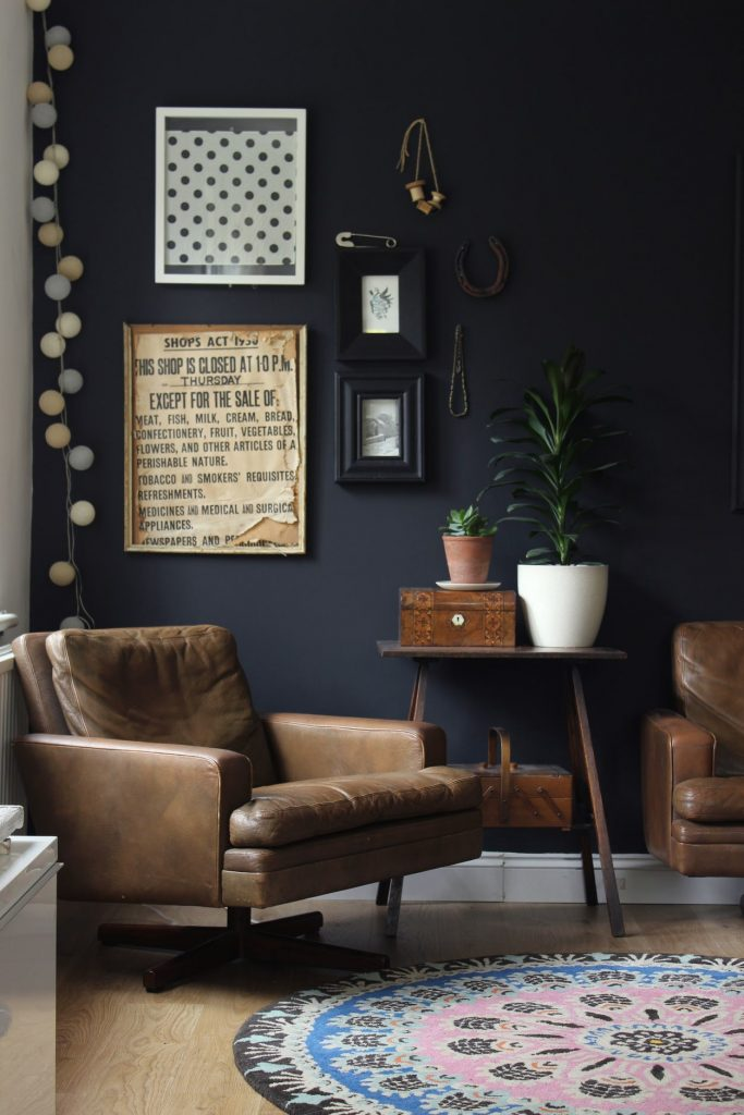A black wall with a brown leather chair and small side table.
