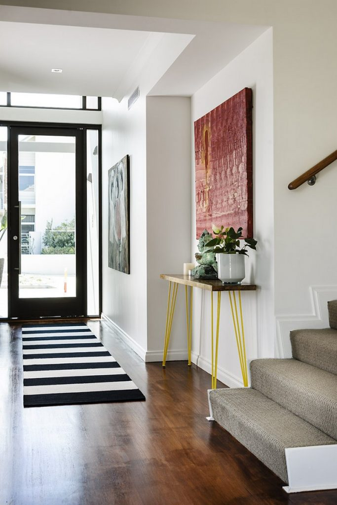 Entryway with console table with bright yellow legs