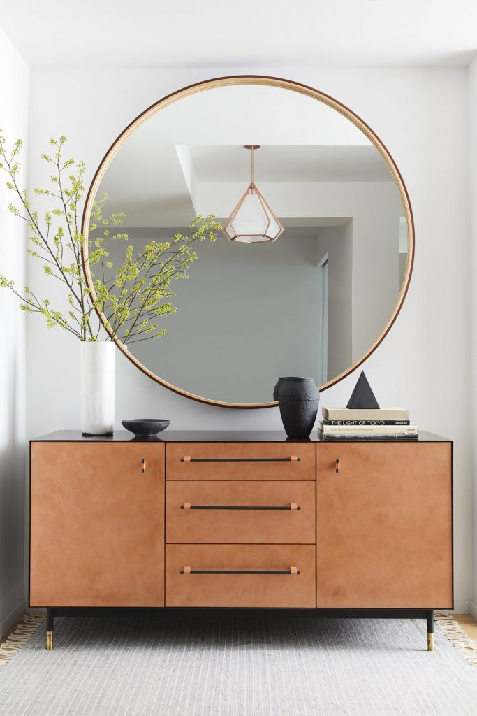 Minimalistic entry table décor with large rounded mirror