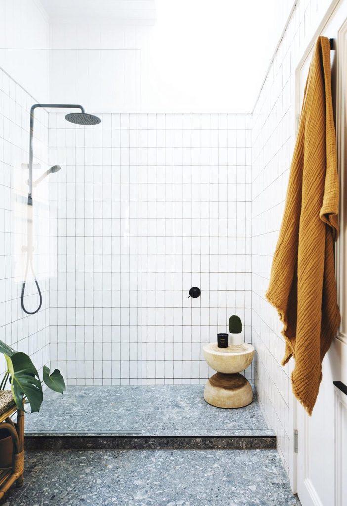 White Shower Tiles with Dark Terrazzo Floor